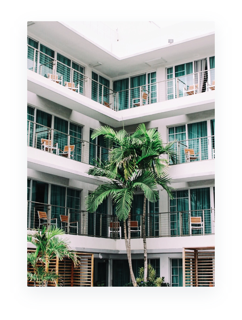 image of several condo units doors overlooking a courtyard filled with palm trees
