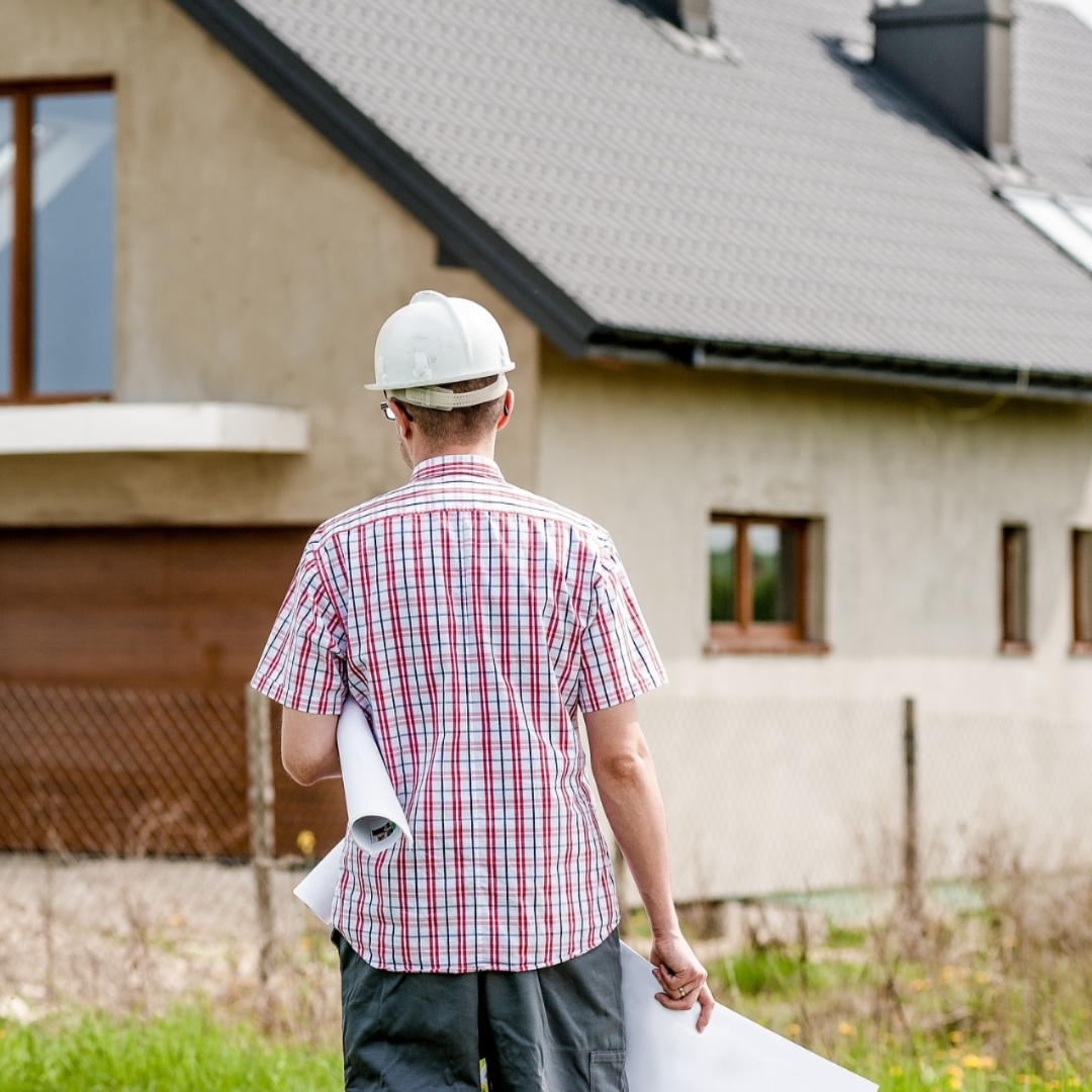 image of a male contractor walking towards a house