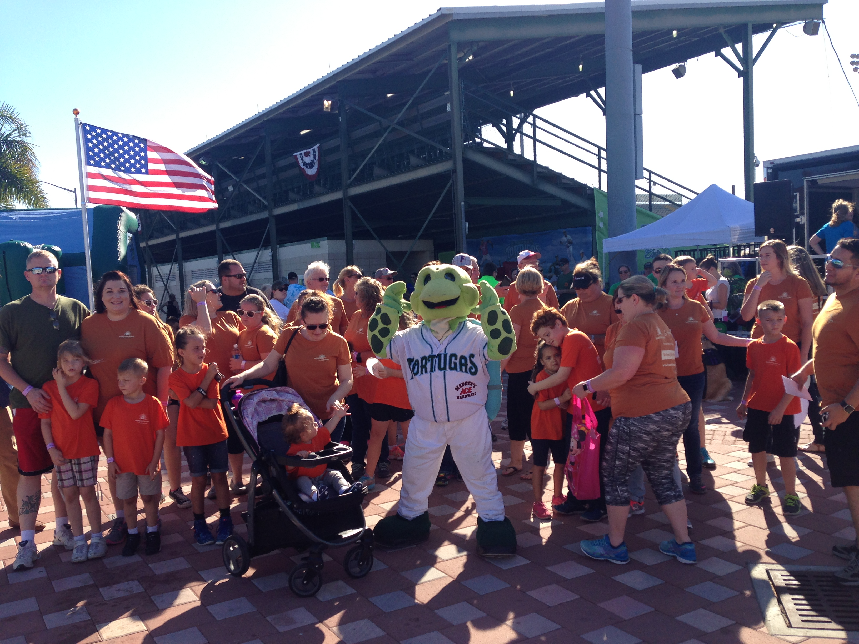 image of the the Tortugas turtle mascot with a group of citizens standing next to him