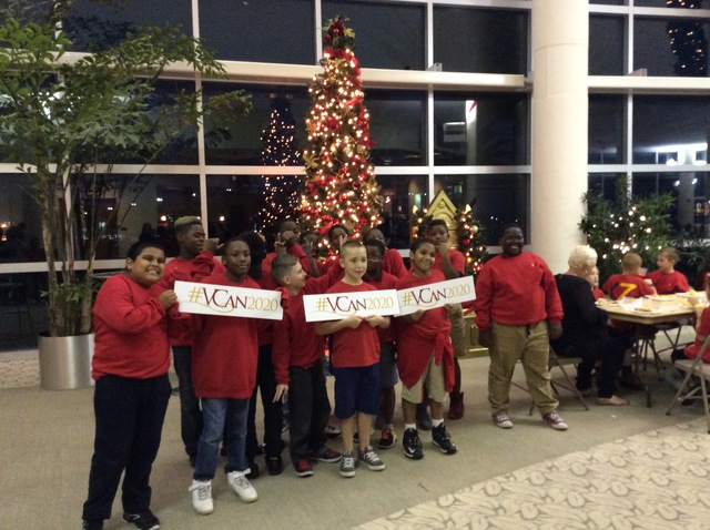 group of school aged children standing in front of a Christmas tree holding a Food Brings Hope sign