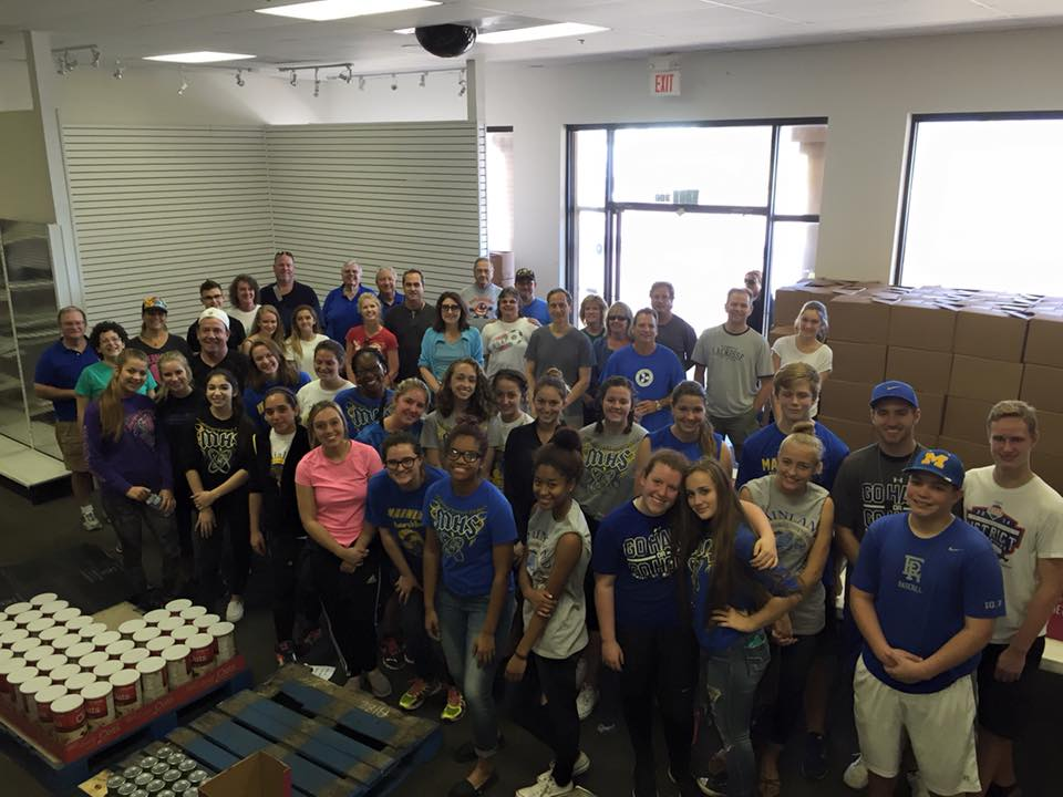 image of a large group of youth volunteers packing up food supplies