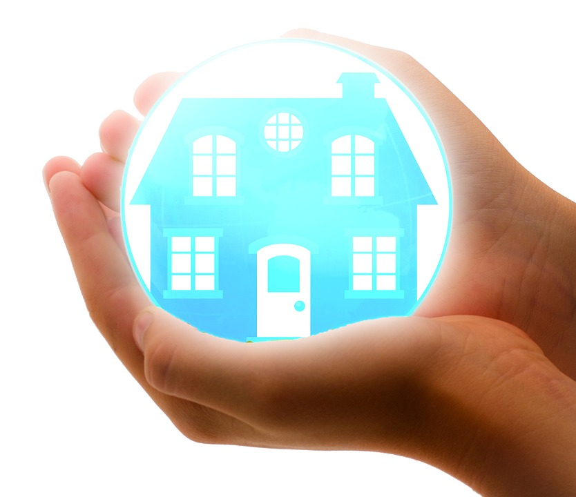 image of a hands holding a glass ball with an image of a house in the middle