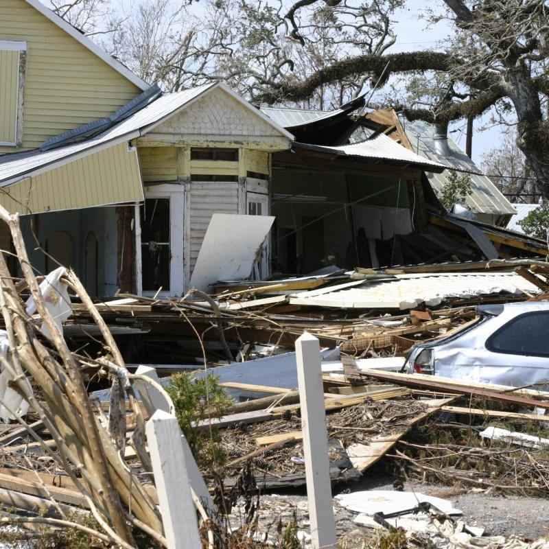 image of a severally home and car with the surrounding yard filled with debris