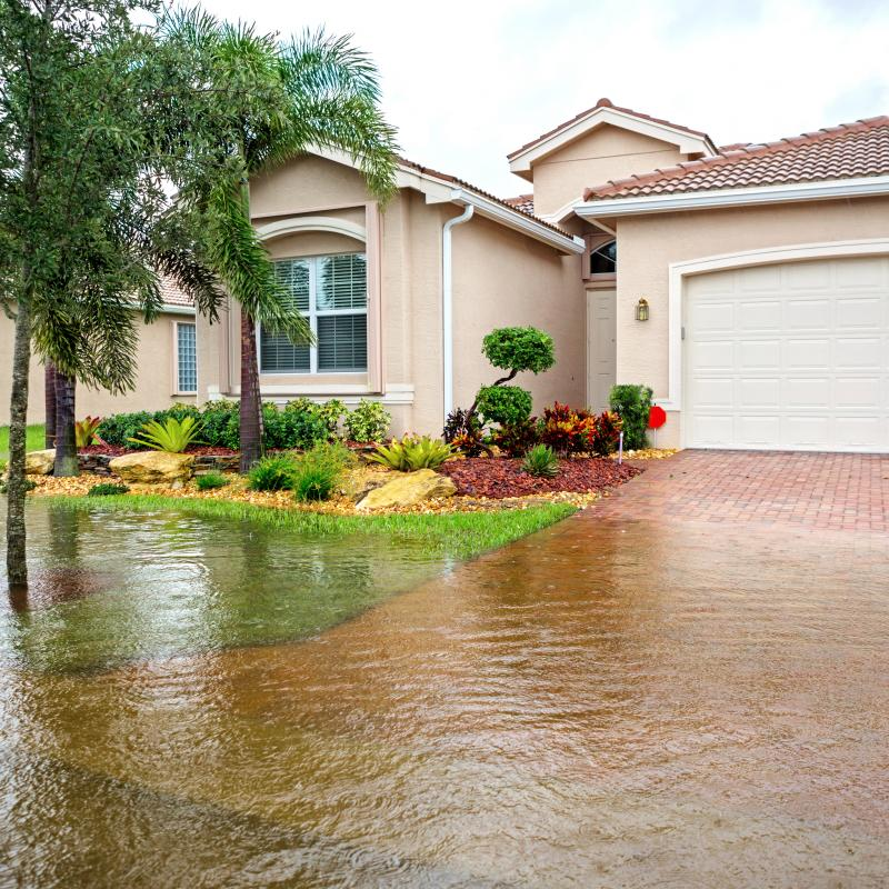 image of a home with a driveway and front yard that is flooded with rain water