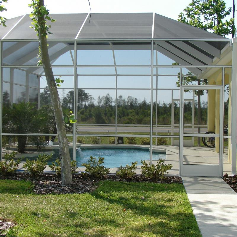 A pool with a screen enclosure attached to the house