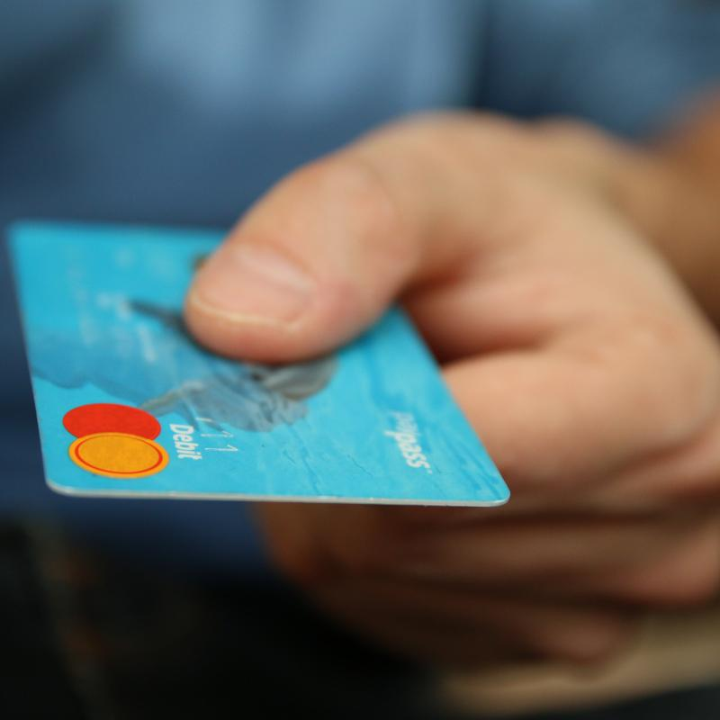Man holding a blue debit card in focus with blurred background