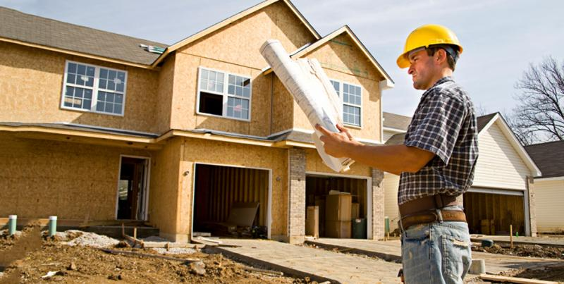 image of a construction working looking at blue prints in front of a new home being built